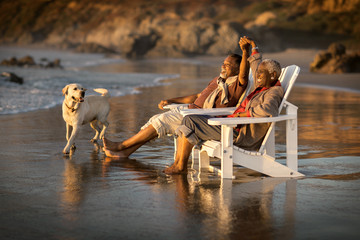 Smiling couple relaxing in deck chair on beach at sunset