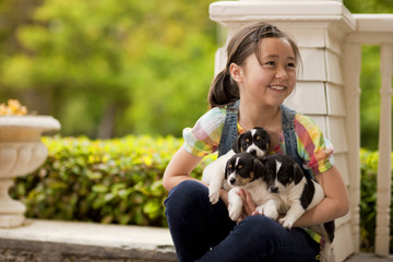 Portrait of young girl on front stoop with a litter of puppies.