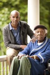 Portrait of senior man and his adult son on verandah.