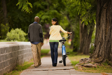 Young woman looks over her shoulder and smiiles and pushes a bicycle along as she walks down a residential street with a young man.