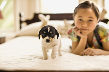 Little girl rests on her chin on her hand as she lies on a bed with a puppy to pose for a portrait.
