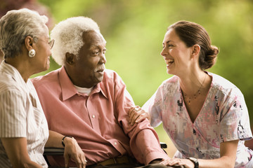Senior couple talk with a smiling nurse as they sit together outside.