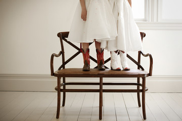 Two girls standing on a chair while dressed up in party clothes and cowboy boots.