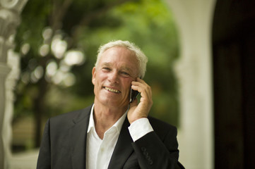 Businessman smiles and uses a cell phone as he poses for a portrait.