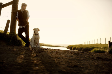 Teenage boy leaning on a fence post while standing next to his dog near a dirt road on a farm.