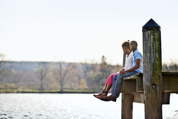 Couple sitting together on wharf.
