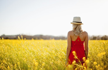 Woman in a red dress standing in a meadow.
