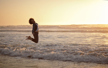 Portrait of a laughing woman leaping into the air while standing at the edge of the sea on a beach.