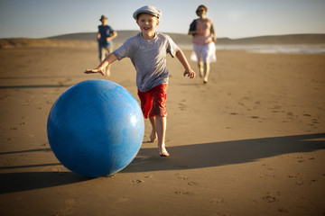 Portrait of a smiling young boy chasing a swiss ball along a sandy beach with his family.