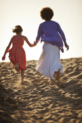 Young girl and her mother holding hands as they walk to the top of a sand dune in the sunshine.