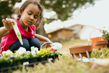 Young girl looking at some plants ready to be planted in the garden.