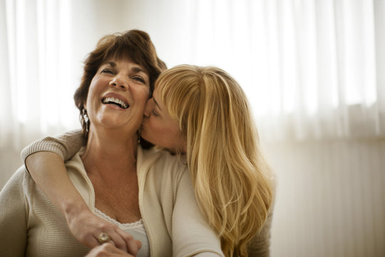 Mature woman laughing as her daughter kisses her on the neck.