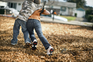Two young boys playfully fighting for the same swing at the playground.