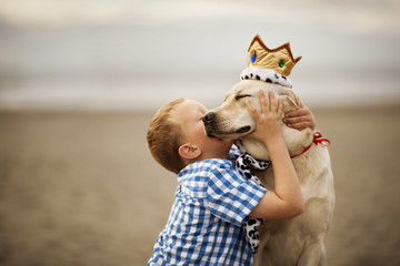 Small boy hugging and kissing his dog at the beach.