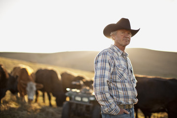Portrait of farmer standing on a paddock with cows in the background.