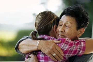Senior woman receiving a hug from her granddaughter.