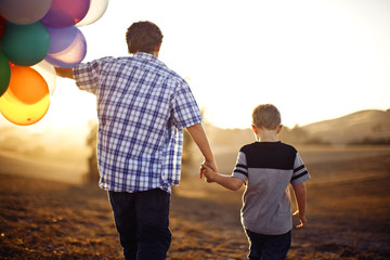 Two brothers walking holding hands, while one holds a large bunch of balloons.