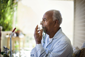 Unwell elderly man uses oxygen mask.