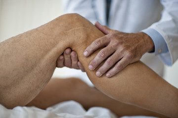 Doctor's hands examining a patient's knee.