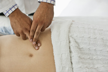 Doctor's hands examining a female patient's abdomen.