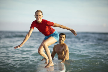 Mid-adult woman learning how to surf with the help of her boyfriend.