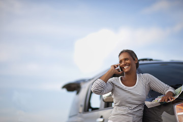 Woman talking on cell phone, leaning against car.