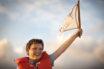 Young boy wearing a life jacket waves a flag.