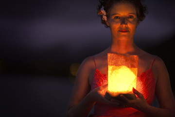 Woman holding a glowing lantern looking into the camera.