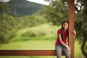 Portrait of young girl sitting on verandah in a rural setting.