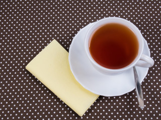 White cup of tea standing on a napkin
