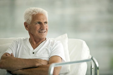 Portrait of senior male patient in a hospital bed looking worried.