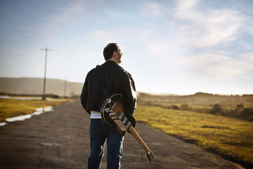 Man walking along a rural road with an electric guitar on his back.