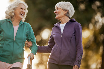 Smiling adult woman helping her friend to walk with a walking frame in a park.