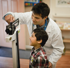 Doctor measuring young patient's weight on medical scales.