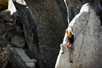 Woman climbing large rock-face.