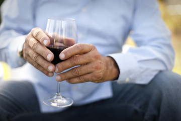 Man sitting down with a glass of wine.