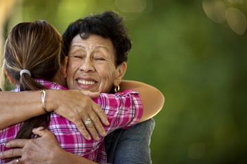Senior woman excitedly hugging her granddaughter.