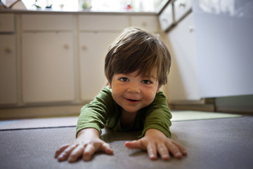 Happy toddler crawling on kitchen floor.