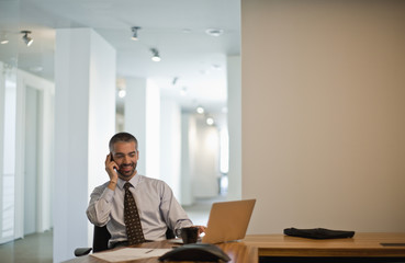 Businessman sits at desk talking on cellphone.