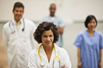 Portrait of mature female doctor smiling with stethoscope around her neck, standing in front of her medical team.
