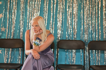 Teenage girl sitting on chair in evening gown, looking bored at prom.