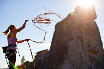 Rock climber preparing rope for climbing.
