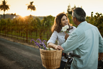 Happy mature couple putting flowers in basket of their bicycle.