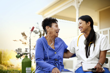 Female nurse sitting with the patient in garden with an oxygen tank