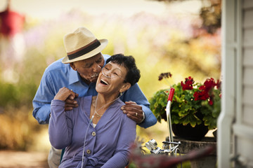 Senior man kissing his wife with nasal cannula on the cheek.