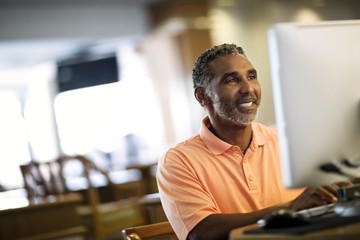 Smiling mature man working on a computer in an office in his home.
