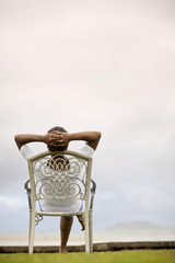 Mid-adult woman sitting in an outdoor chair with her hands behind her head.
