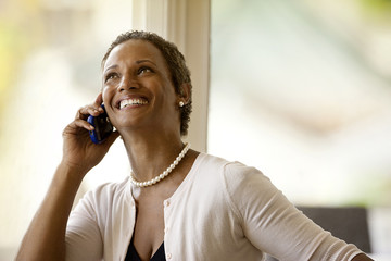 Smiling businesswoman listening on cell phone.