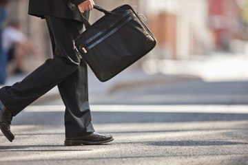 Businessman in a suit and holding a briefcase leaps into the air in a narrow empty street.