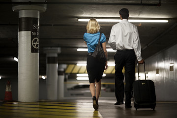 Two business colleagues walking through an underground parking building.